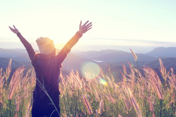 Happy Woman Enjoying Nature on grass meadow on top of mountain c
